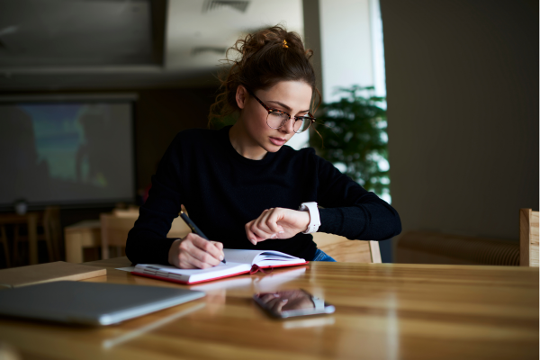 student checks the time on her watch whilst studying at her desk