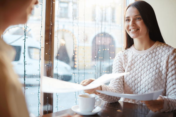 Woman hands resume and cover letter to another woman in a cafe