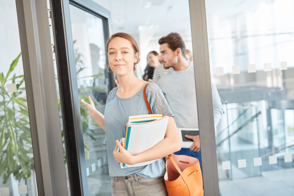 young student walking into classroom holding notes