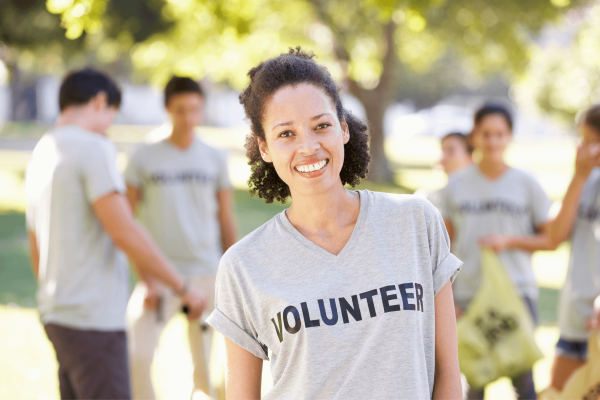 Woman standing in front of group wearing volunteer shirt