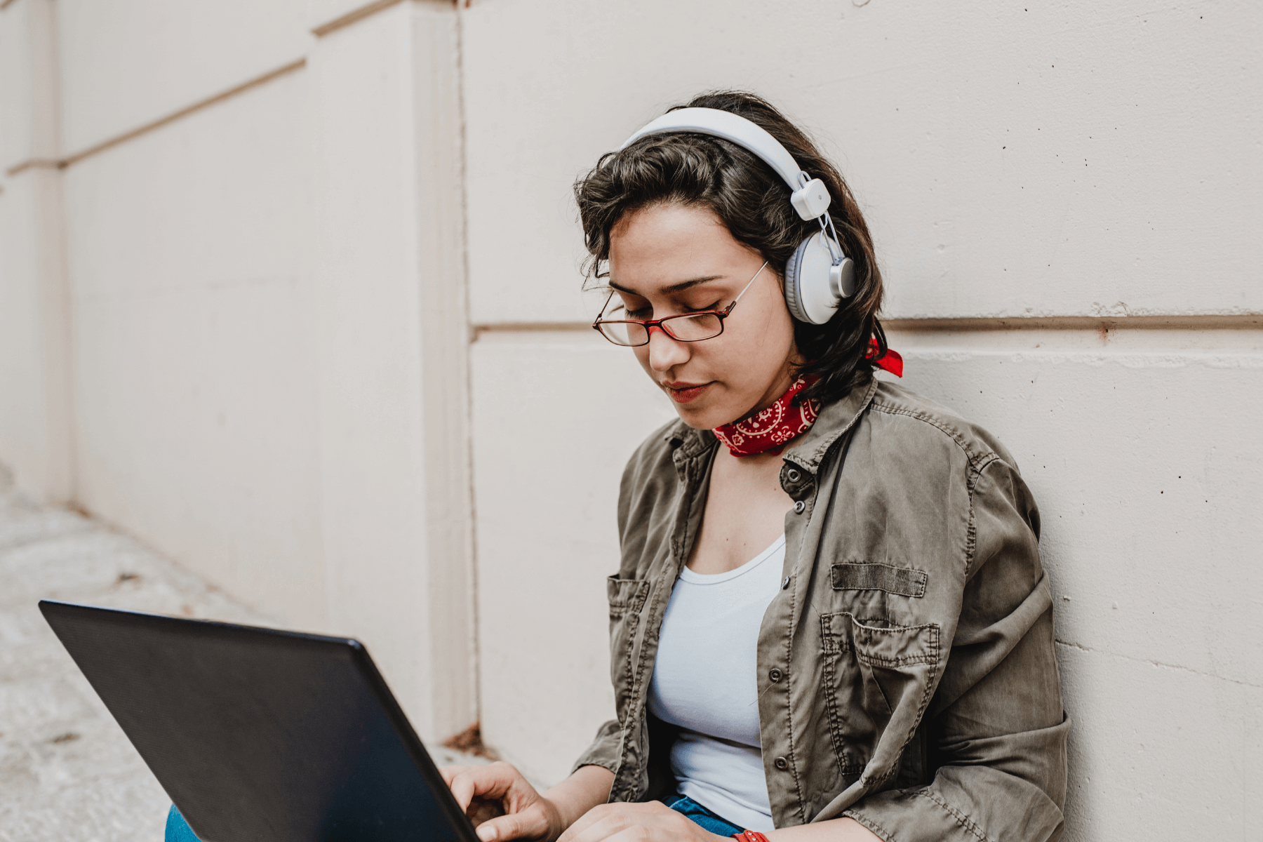 Young woman wearing headphones uses laptop to look for a new job after redundancy
