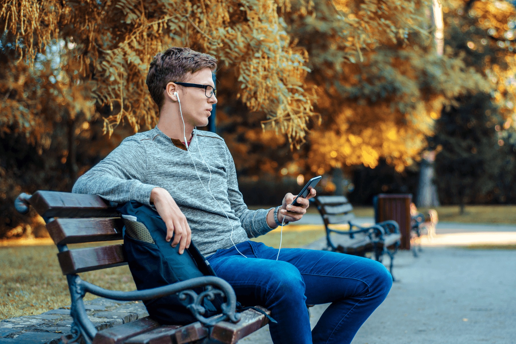 young male introvert sits on park bench listening to music
